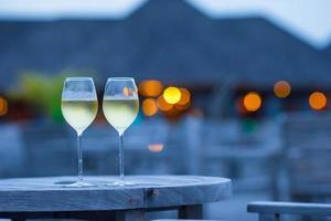 twee glazen smakelijke witte wijn bij zonsondergang foto