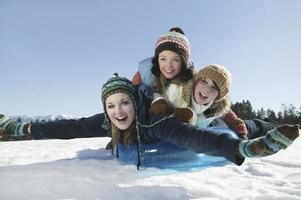 vrienden rodelen in de winter foto