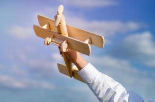 hand van een kind spelen met een houten vliegtuig speelgoed foto