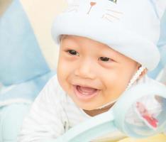 babyjongen glimlachend en toont zijn eerste tanden foto