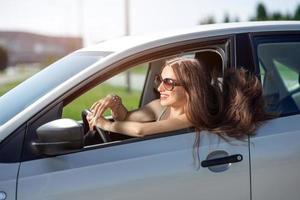 jonge lachende vrouw haar nieuwe auto rijden foto