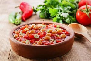 gekookte kikkererwten met tomaten in een kom foto