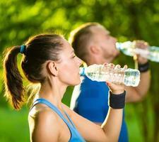 man en vrouw drinkwater uit de fles na fitness sport foto