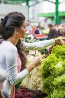 mooie jonge vrouw groenten op de markt kopen foto