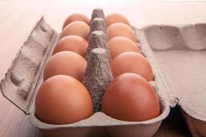 bruine eieren in eierdoos op keukentafel foto