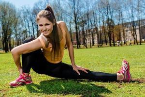 vrouw die uitrekkende oefening in openlucht doet foto