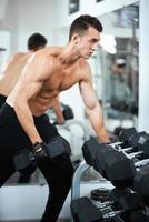 man doet oefeningen halter biceps spieren foto