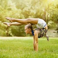 jong meisje dat uitrekkende oefening op groen gras bij park doet foto