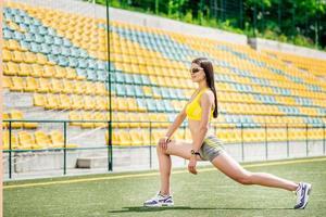 succesvolle atleet warming-up op het veld in zonnige dag foto