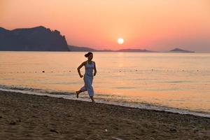 vrouw doet ochtend oefeningen op zee tijdens zonsopgang foto