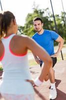 jonge atletische man en vrouw die zich uitstrekt buiten foto