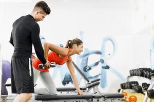jonge mannelijke trainer die instructies geeft aan een vrouw