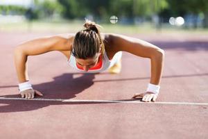 jonge mooie vrouw doet push-ups buitenshuis op zomerdag foto