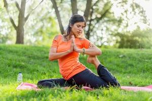 actieve vrouw doet yoga houdingen bij zonsondergang foto