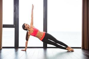 vrouw doet yoga-oefeningen in de fitnessruimte foto