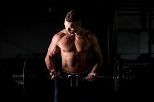 jonge man tillen een halter in de sportschool foto