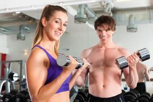 sport - paar oefent met barbell in de sportschool foto