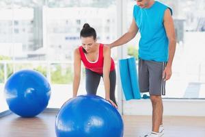 trainer die vrouw helpt met haar oefeningen bij gymnastiek foto