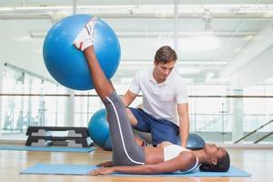 persoonlijke trainer die met de oefeningsbal van de cliëntholding werkt foto