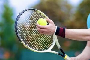 close-up van handen van professionele mannelijke tennisser met raquet foto