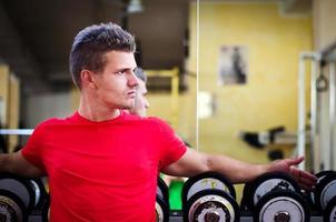 knappe jonge man in de sportschool zittend op halters rek foto