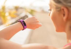 vrouw fitness wearable apparaat controleren foto