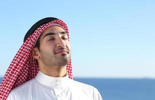 Arabische Saoedische man ademen diep frisse lucht op het strand foto