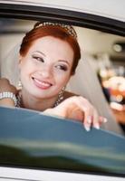 jonge lachende blanke bruid in witte limo.