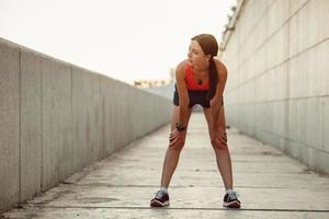 jonge blanke vrouw ademhalen na het joggen foto