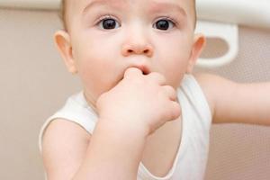 leuke blanke baby met vinger in zijn mond foto