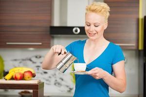 mooie jonge Kaukasische blonde vrouw espresso koffie koken foto