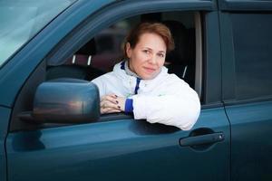 jonge blanke vrouw als chauffeur in een grote auto foto