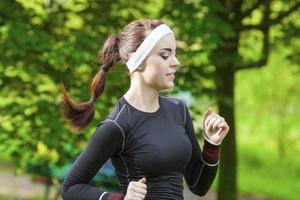 portret van glimlachende Kaukasische sportvrouw die haar regelmatige opleiding in openlucht heeft. foto