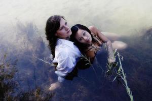 Kaukasische en Aziatische Amerikaanse vrouwen zitten in de rivier foto