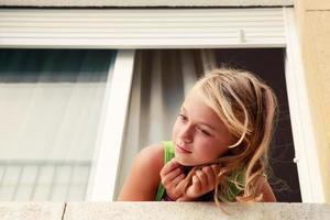 klein blond Kaukasisch meisje in het venster, openluchtportret foto