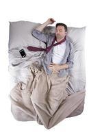 blanke man slapen met mobiele telefoon alarm in bed foto