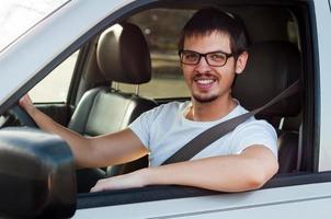 mannelijke Kaukasische goede chauffeur lacht in zijn auto foto