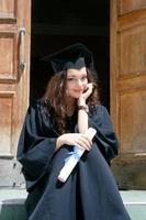 jonge Kaukasische lachende student in jurk in de buurt van de universiteit