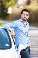 Latijns-Amerikaanse chauffeur zittend op de zijkant van zijn auto