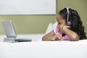 klein meisje kijken naar draagbare dvd-speler