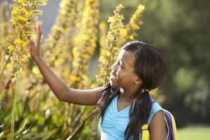 meisje dat bloemen bekijkt foto