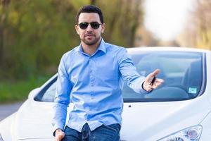 Latijns-Amerikaanse bestuurder die autosleutels houdt die zijn nieuwe auto drijven