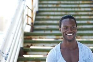 Afro-Amerikaanse mannelijk model glimlachend buitenshuis foto