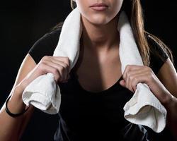 fitness meisje met handdoek geïsoleerd op zwart detail foto