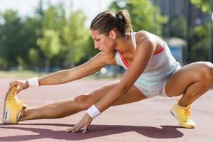 mooie jonge atletische vrouw die zich uitstrekt in de zomer