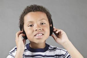 jongen die aan hoofdtelefoons luistert foto