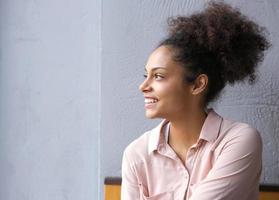 en Afrikaanse Amerikaanse vrouw die weg glimlacht kijkt foto