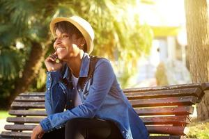vrolijke jonge Afro-Amerikaanse vrouw buiten zitten foto