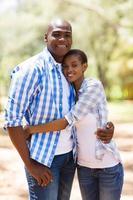 jonge Afrikaanse Amerikaanse echtpaar knuffelen in het bos foto