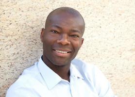 Afrikaanse man op een muur camera kijken